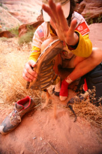 A racer empties sand from her shoe