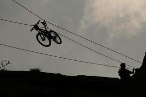 A mountain bike travels down a zipline by itself