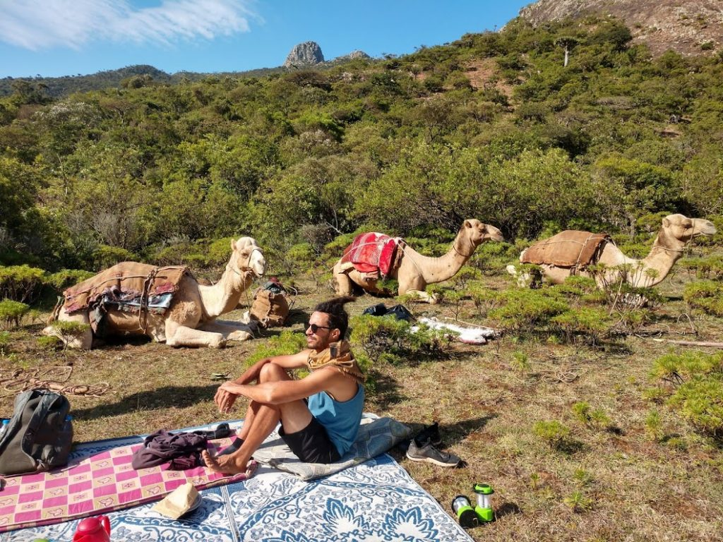 Alex sitting with camels in our campsite
